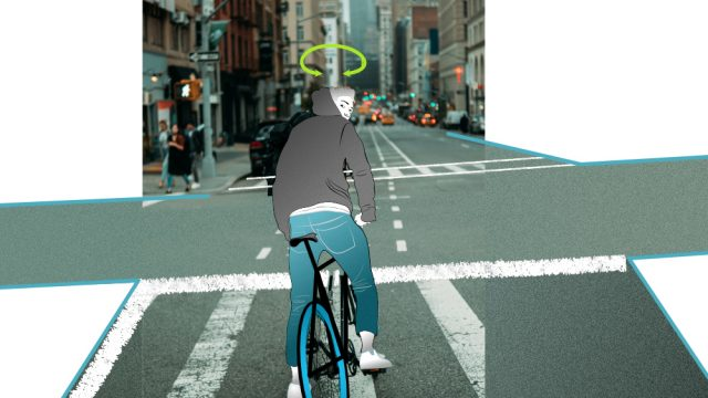 A cyclist at an intersection looking around